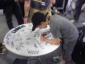 Finley Mapelstone signing the giant Hall of Fame Drum Head for Shine Drums at the London Drum Show 2010